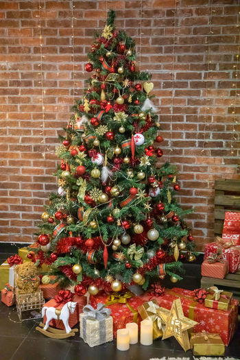 View of christmas tree against brick wall