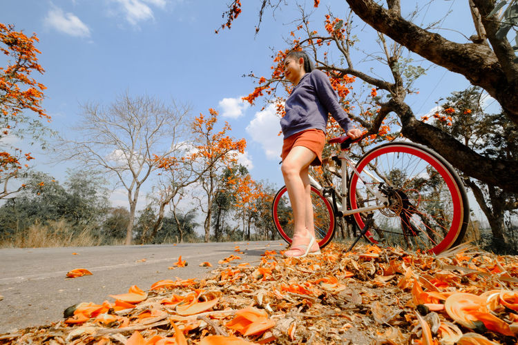 Woman with bicycle on leaves during autumn