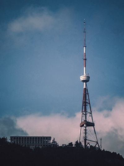 Low angle view of communications tower and buildings against sky