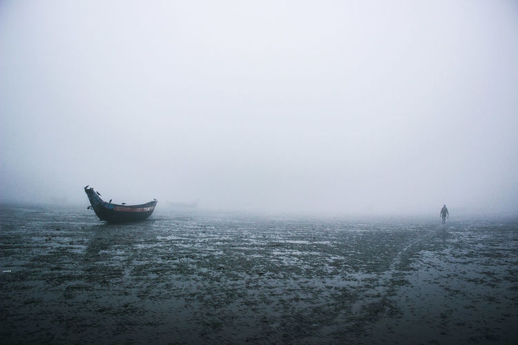 Boat on shore in foggy weather