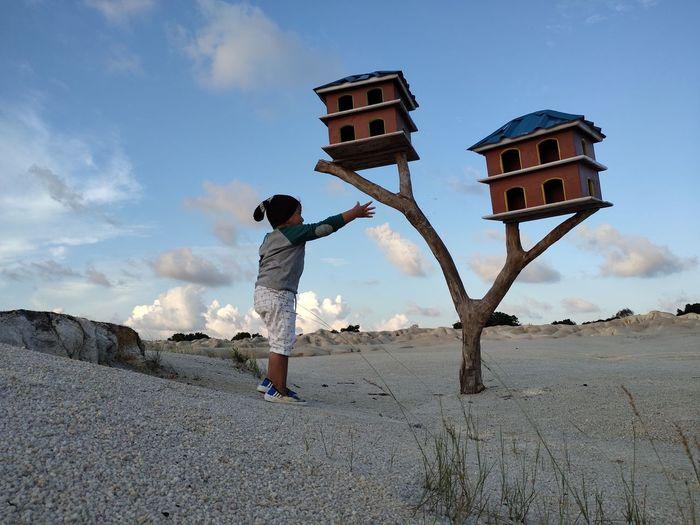 Full length of boy standing on land against sky