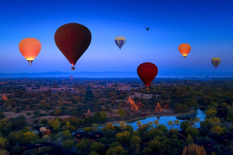 Hot air balloons flying over landscape against blue sky