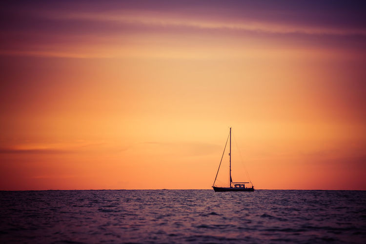 Silhouette Sailboat Sailing On Sea Against Sky During Sunset