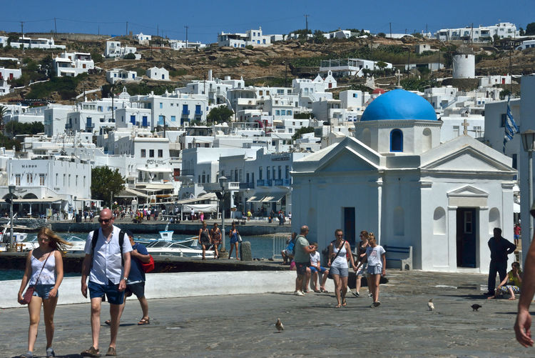 cityscape of Mykonos with church and tourists walking around Building Exterior Architecture Group Of People Built Structure Crowd City Real People Building Men Large Group Of People Day Women Sunlight Nature Lifestyles Adult Leisure Activity Outdoors Residential District Mykonos,Greece Tourists Walking Around Church Greek Architecture Cityscape Urban White Buildings Blue Dome Summertime Holiday