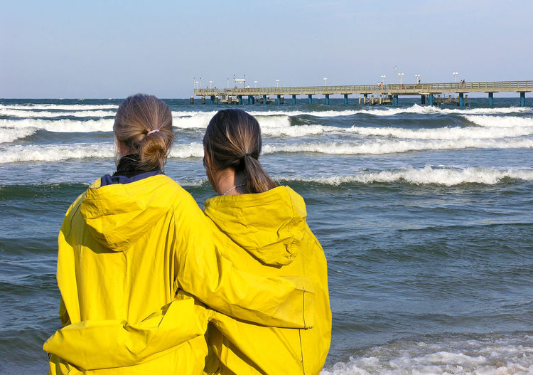 Two girls on a beach of Rügen, Ostsee Happy Nature Ostsee Rügen View Weather Young Beach Destination Embracing Friendship Germany Girls Health Leisure Activity Nature Outdoors Raincoat Rear View Sea Vacations Water Wave Women Yellow
