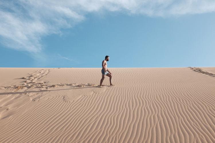 Full Length Of Man Walking On Sand Dune In Desert
