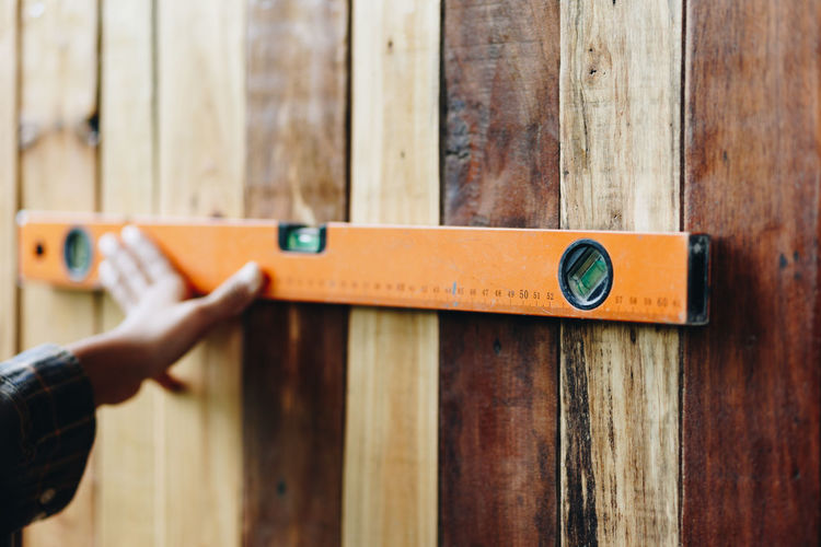 Cropped hand measuring wooden wall