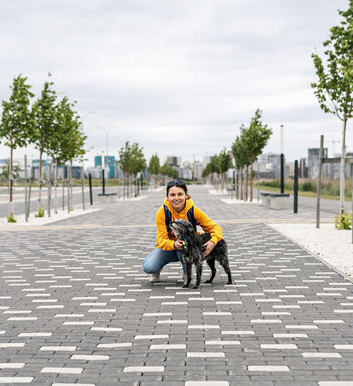 Smiling young woman in yellow hoodie hugging fluffy shaggy gray dog on alley, pet love, walking dog