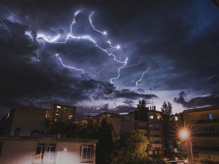 Low angle view of lightning in city against sky at night