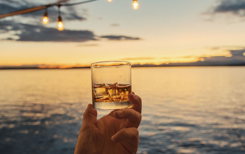 Close-Up Of Hand Holding Whiskey Glass Against Sea During Sunset