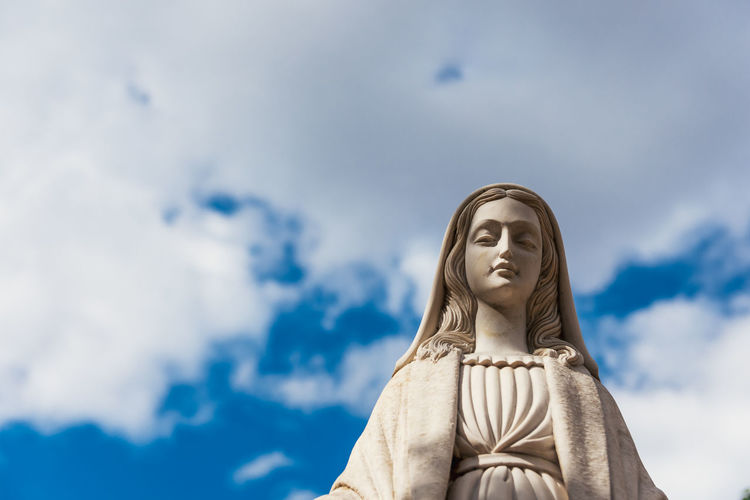 Marble figure of the virgin mary. blue sky background.