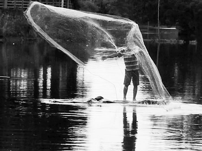Spreading the fishing net Water Reflection Waterfront Real People Lake Fishing Men Transportation Vertebrate Fisherman Lifestyles Occupation Fishing Industry Day One Person Outdoors Fishing Net Nature Nautical Vessel