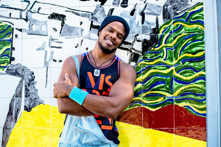 Happy young man standing against graffiti wall