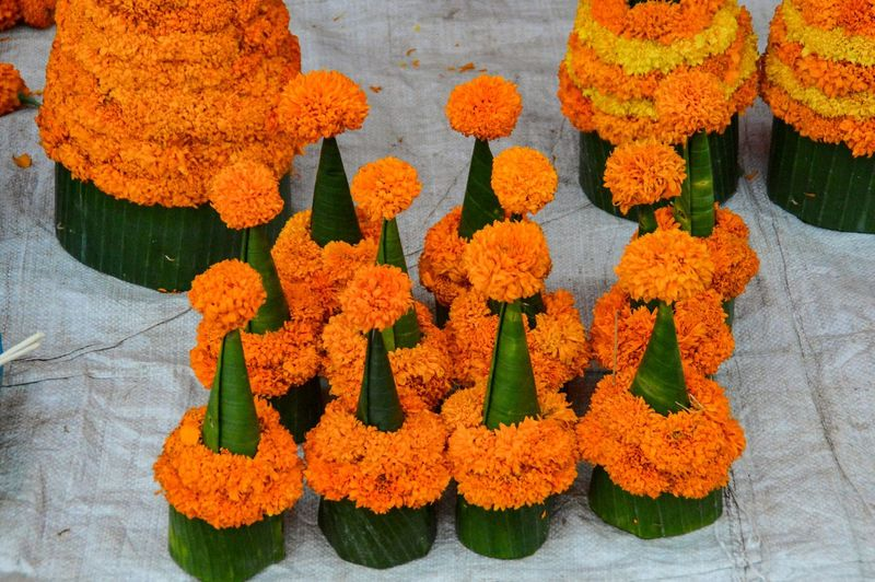 High Angle View Of Religious Offerings Made From Marigold Flowers And Banana Leaves