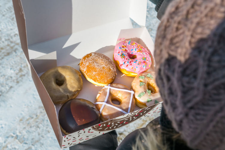 Close-up high angle view of woman holding various donuts in box