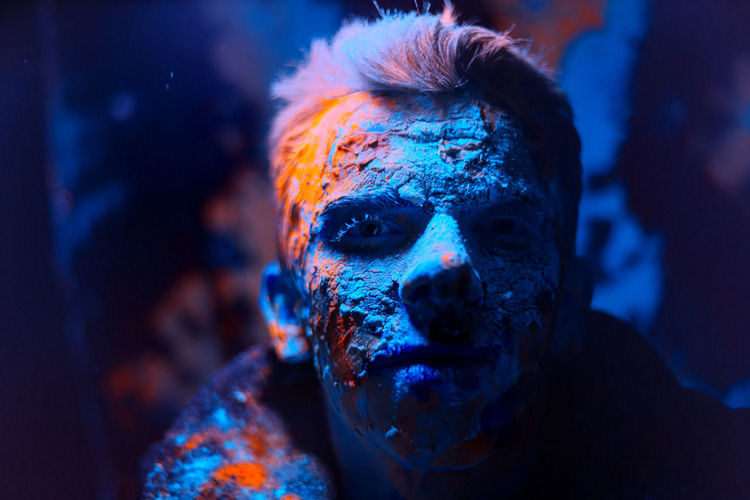 Close-up portrait of man covered with powder paint against black background
