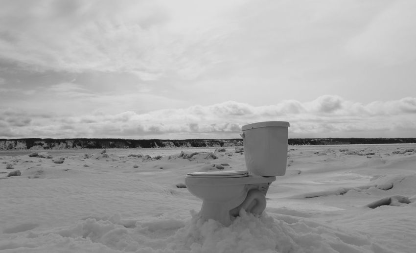 Abandoned commode on snow covered landscape