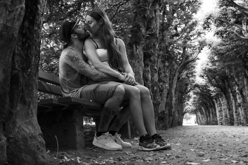 Couple Kissing While Sitting On Bench At Park