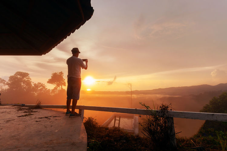 Rear View Of Man At Gazebo Photographing Mountains During Sunset