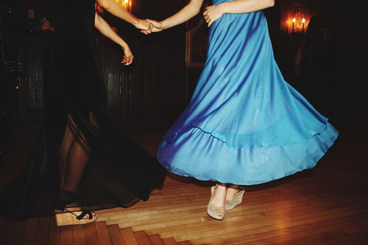 Low Section Of Female Friends Dancing On Hardwood Floor