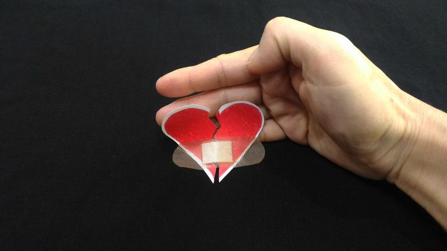 Cropped hand holding torn heart shape paper with bandage against black background