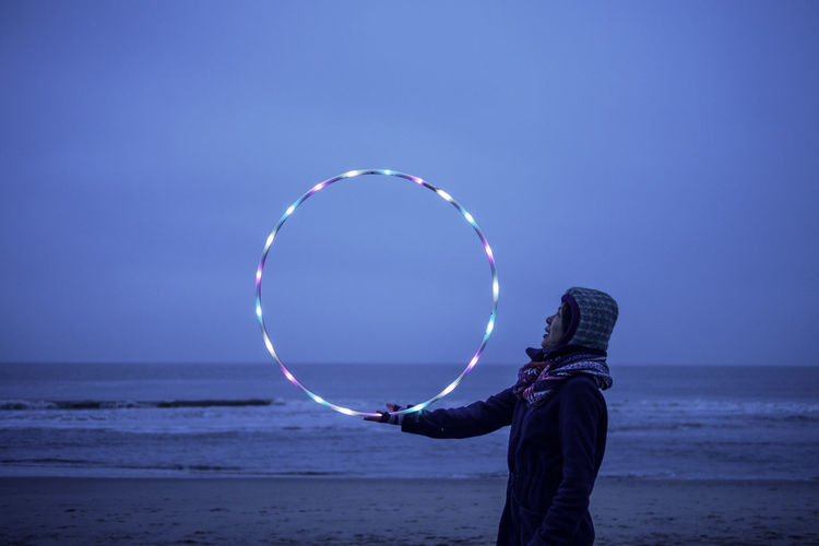 Side view of woman holding illuminated plastic hoop at beach against clear sky at dusk
