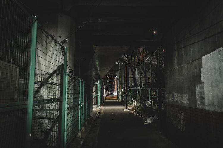 Empty Street Amidst Fence At Night