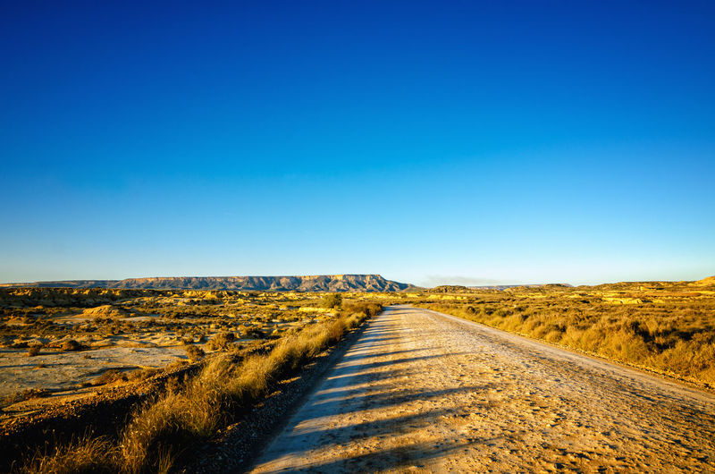 Dirt road along countryside landscape against clear blue sky