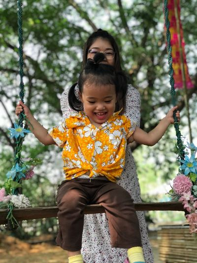 Mother swinging daughter on swing at park