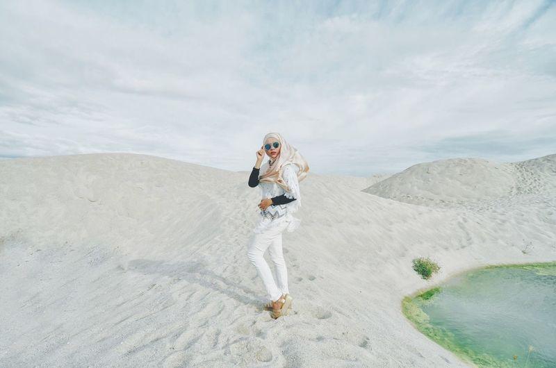 Full length of woman standing at desert