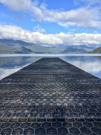 Low angle view of jetty at Lake Kaniere, West Coast, New Zealand. Beauty In Nature Cloud - Sky Day Idyllic Landscape Mountain Mountain Range No People Non-urban Scene Outdoors Scenics Sky Tranquil Scene Tranquility Water