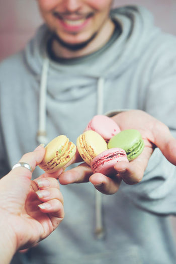 Holding One Person Front View Food And Drink Midsection Focus On Foreground Freshness Real People Food Men Hand Indoors  Close-up Human Hand Lifestyles Smiling Showing Casual Clothing Human Body Part Temptation Macaroon Macarons Dessert Delicious Temptation