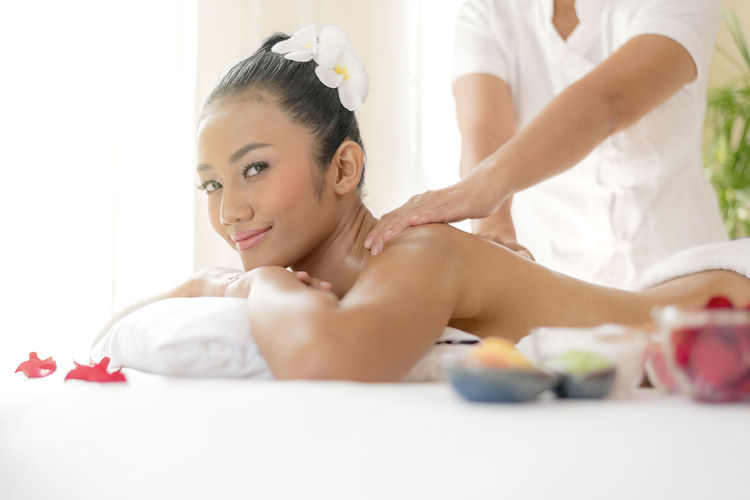 Portrait Of Shirtless Woman Receiving Massage From Therapist