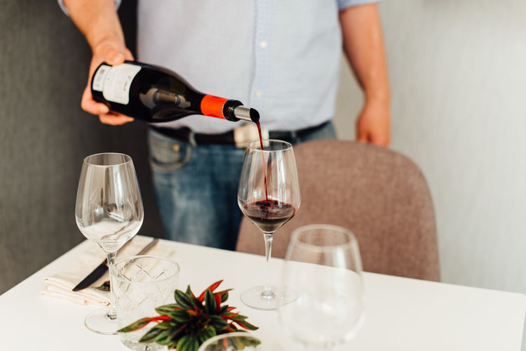 Midsection of man pouring wine in glass on table