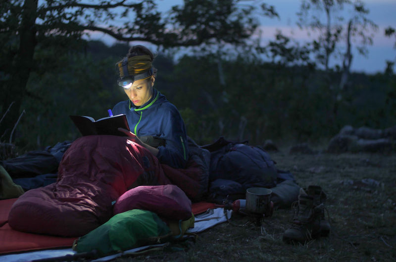 caucasian female hiker reading book/writing journal at night while wildcamping, strong light from headlamp Backpacking Camping Headlamp Hiking Light Reading Travel Trekking Woman Writing Activity Adventure Beam Book Caucasian Clothing Day Evening Female Focus On Foreground Forest Front View Full Length Hobby Journal Land Leisure Activity Lifestyles Men Nature Night Outdoors People person Plant Real People Sitting Sleeping Sleeping Bag Tree Young Adult