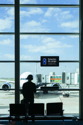 Rear view of man looking through window at airport
