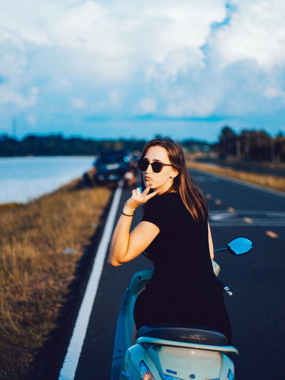Portrait of young woman showing peace sign while sitting on motor scooter at road