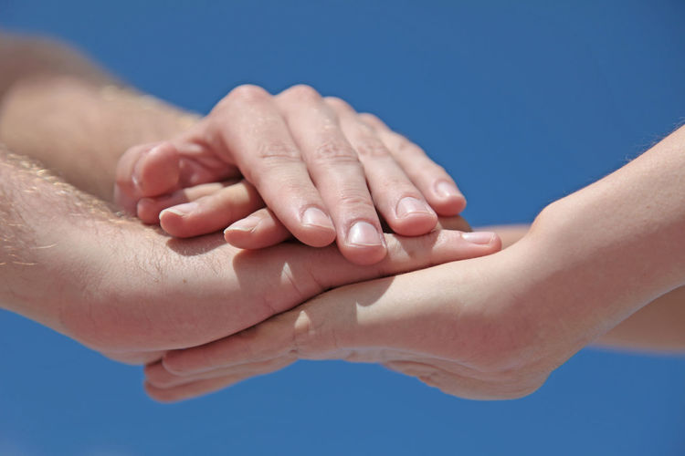 Cropped image of people stacking hands against clear blue sky