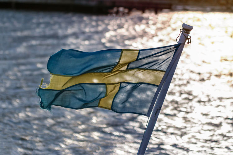 Close-up of worn out swedish flag on small boat
