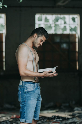 Side view of shirtless young man reading book standing at home