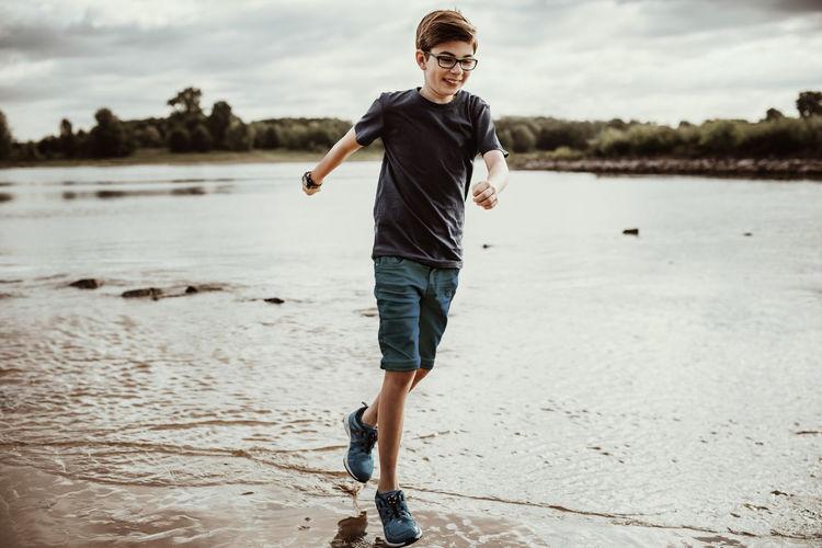Full length of boy running on lakeshore