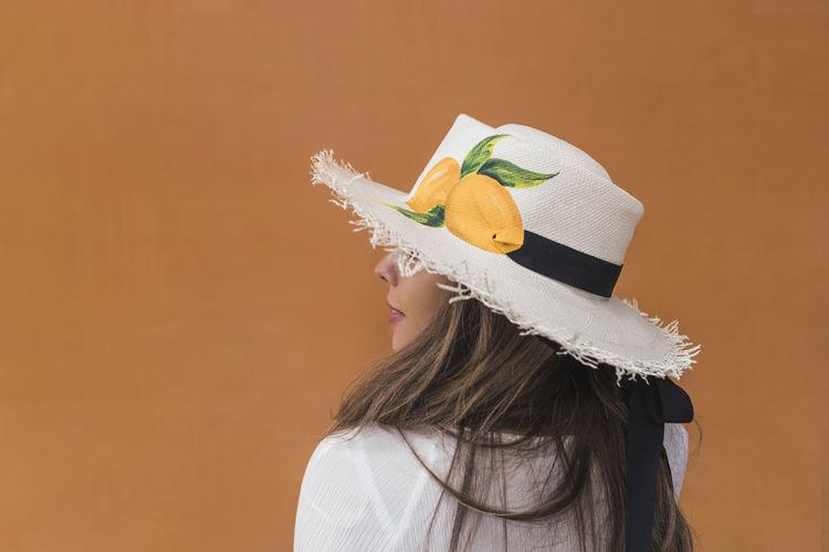 Portrait of woman wearing hat against orange background