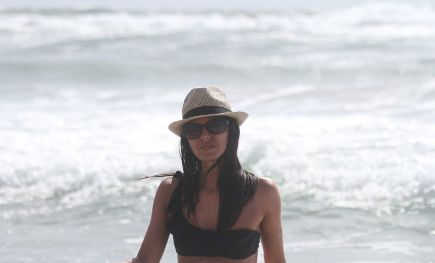 Portrait of young woman wearing sunglasses while standing in sea during sunny day