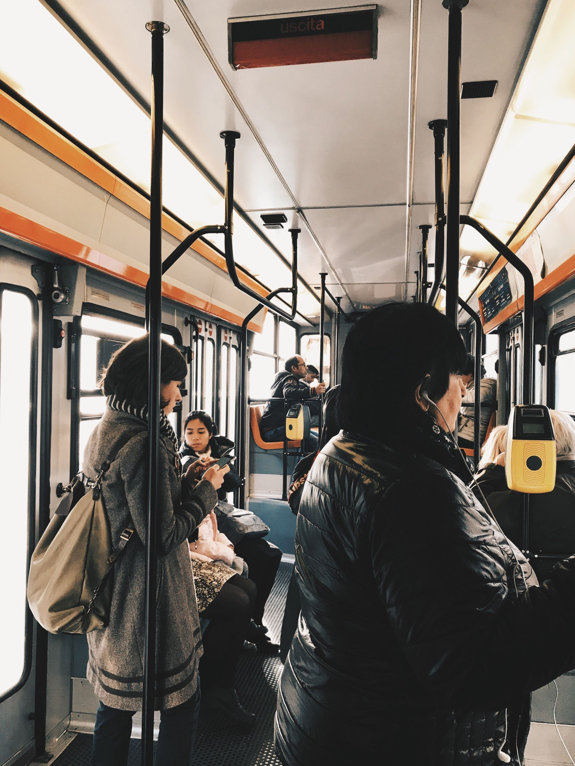 public transportation, transportation, train - vehicle, vehicle interior, journey, passenger, subway train, travel, mode of transport, commuter, rail transportation, real people, passenger train, metro train, commuter train, train interior, vehicle seat, casual clothing, black hair, city life, standing, lifestyles, young adult, bus, women, men, sitting, railroad station platform, young women, indoors, city, technology, day, one person, adult, people