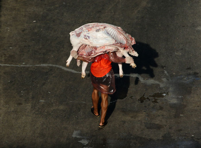 High Angle View Of Man Carrying Raw Meat While Walking On Road