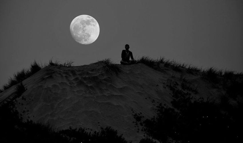 Low angle view of silhouette man against moon in sky