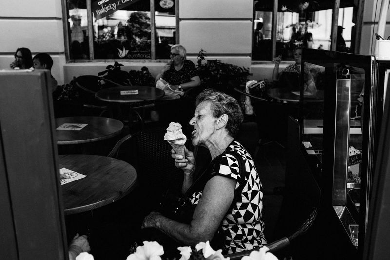 ICE CREAM! The Week on EyeEm Light And Shadow Capture The Moment Fujifilm Street Photography Monochrome The Art Of Street Photography Bnw Eating Ice Cream Black And White Real People Women Sitting Adult Lifestyles One Person Indoors  Seat Leisure Activity Chair Casual Clothing Drink Relaxation Senior Adult Food And Drink Restaurant Business Mature Adult Hairstyle