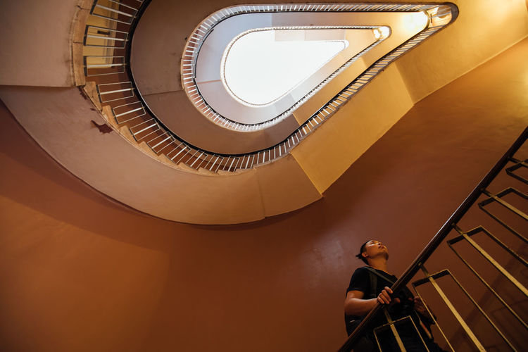 Low angle view of woman standing on spiral staircase