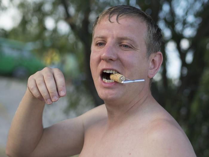 Shirtless Man Holding Cork In Mouth