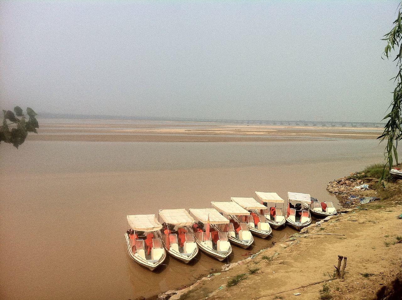Row of boats on beach by sea